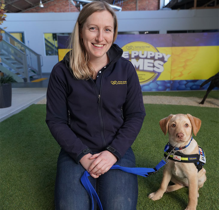 Claire (trainer) and Unique (pup in training) sitting together in mobility centre